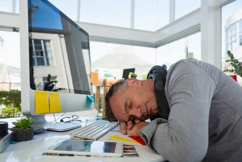 Бизнесмен спать на столе в студии стоковое изображение