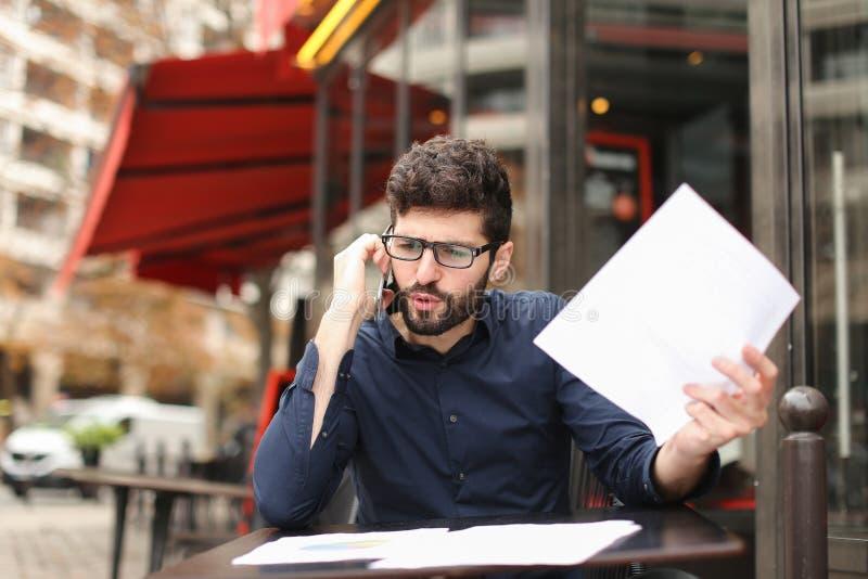 Бизнесмен споря smartphone и читая газеты на плате кафа стоковое фото rf