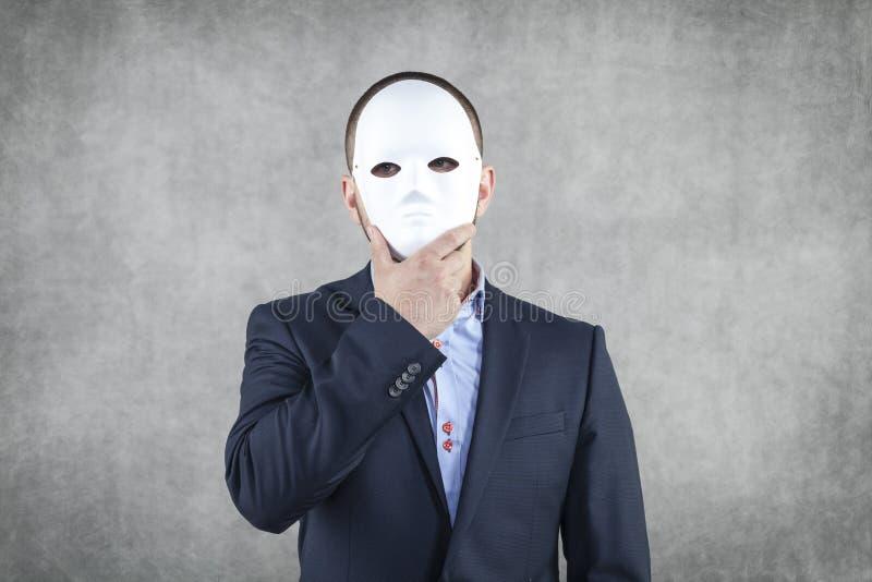 Бизнесмен спрятанный за маской стоковая фотография