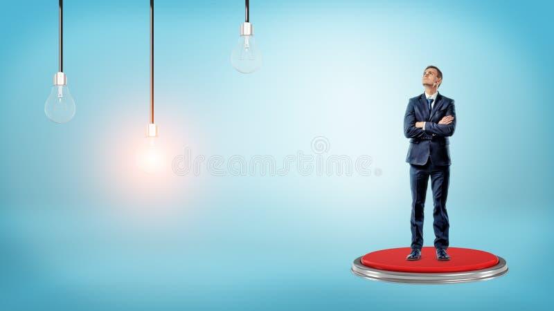 Бизнесмен стоит на кнопке и смотрит до накаляя лампа около 2 других стоковое изображение