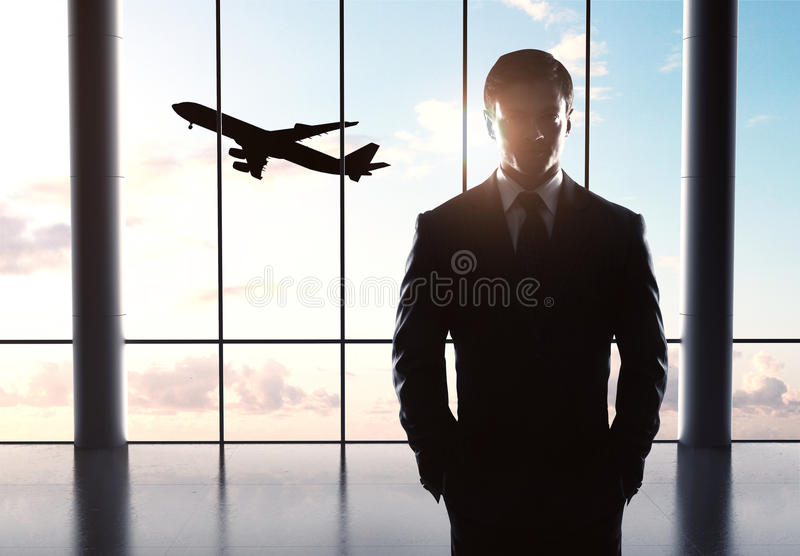 Бизнесмен стоя в авиапорте стоковая фотография