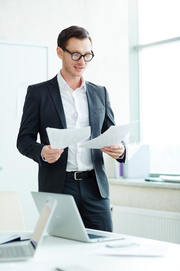 Бизнесмен стоя в документах чтения офиса стоковые фотографии rf