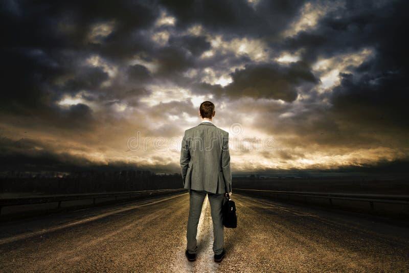 Бизнесмен стоя в середине дороги. стоковое фото rf