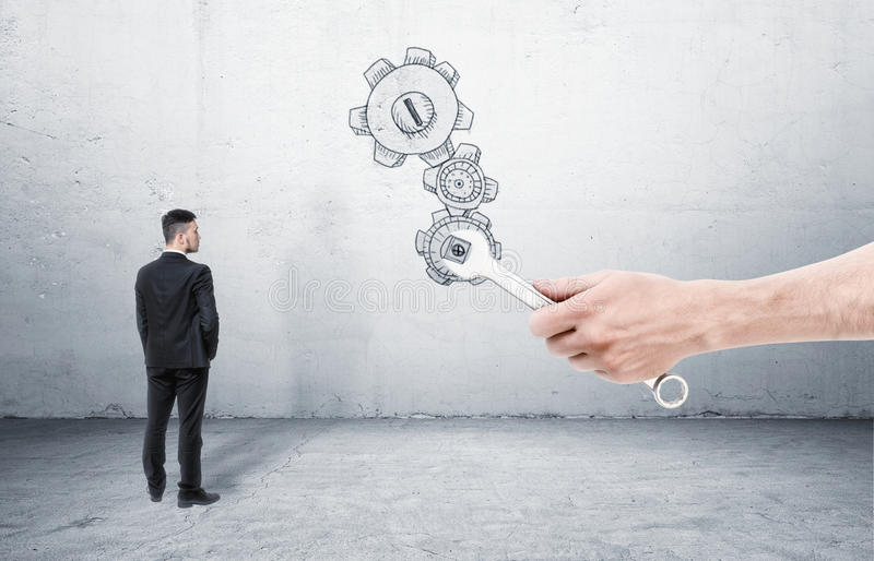 Бизнесмен стоя и смотря сильная рука с ключем, который cogwheel извивов стоковая фотография