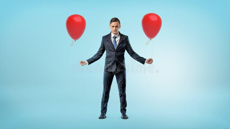 Бизнесмен стоя на голубой предпосылке с красным воздушным шаром в каждой руке стоковые изображения