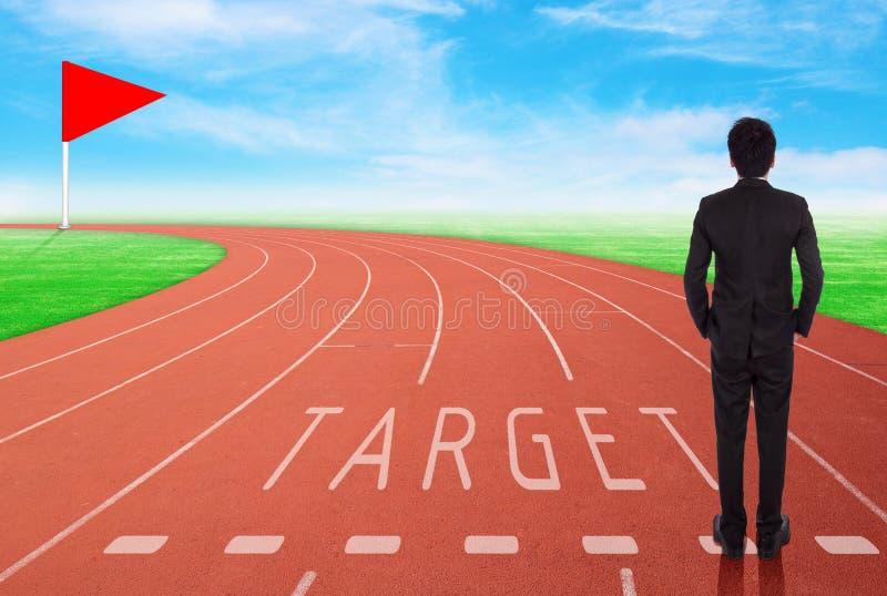 Бизнесмен стоя на идущем следе и смотря к цели стоковое изображение