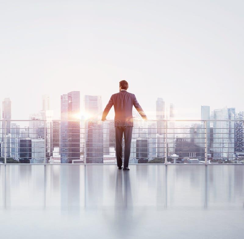 Бизнесмен стоя на крыше стоковое изображение