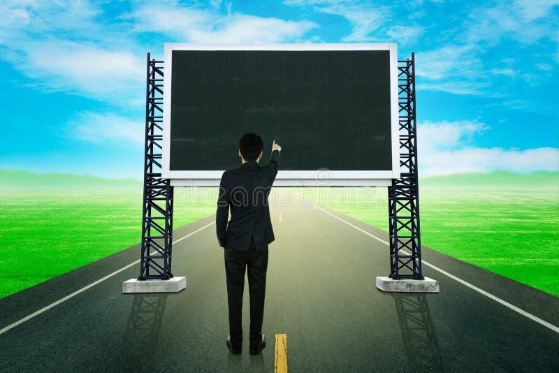 Бизнесмен стоя на дороге и указывая с большим знаком стоковые фото