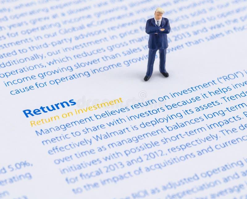 Бизнесмен стоя на отчете о рентабельности инвестиций стоковое изображение rf