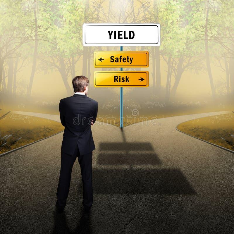 Бизнесмен стоя на перекрестке имея безопасность и риск вариантов стоковые фото