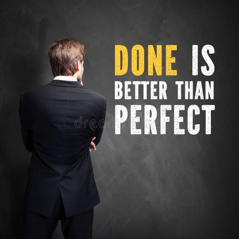 Бизнесмен стоя перед доской при сделанное ` сообщения лучший чем совершенное ` стоковая фотография
