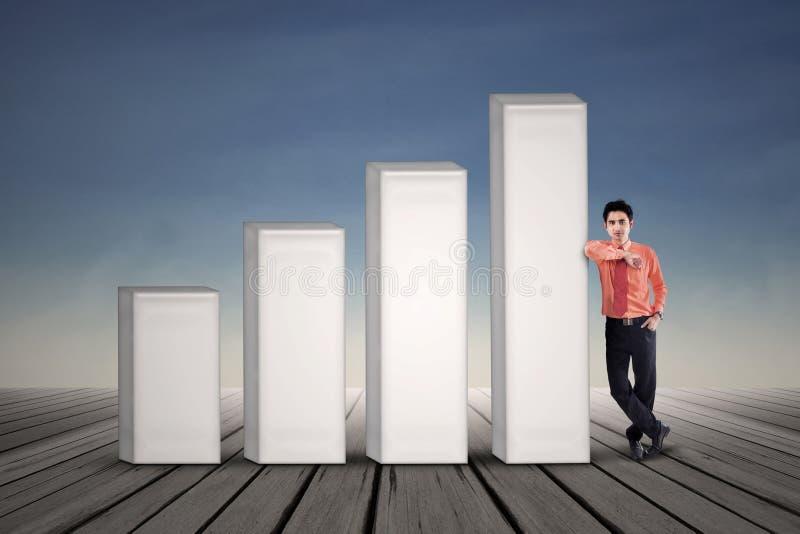 Бизнесмен стоя рядом с диаграммой в виде вертикальных полос на голубом небе стоковые фото