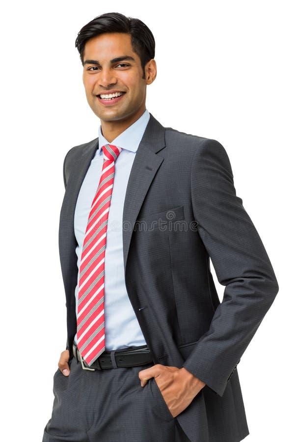 Бизнесмен стоя с руками в карманн стоковая фотография