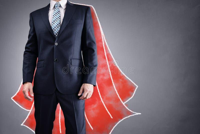 Бизнесмен супергероя с красной концепцией накидки для руководства стоковое изображение
