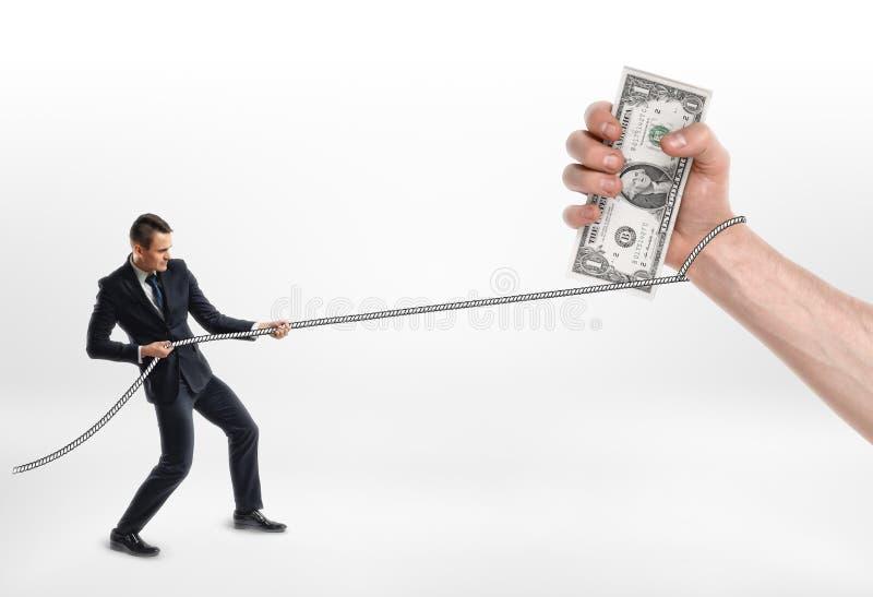 Бизнесмен схватил сильную руку с долларами и тягами наличных денег оно веревочкой стоковые изображения rf