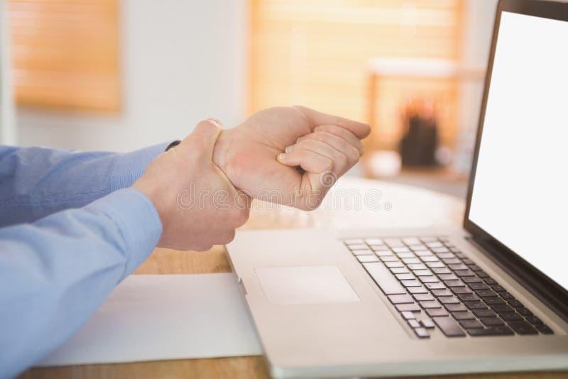 Бизнесмен схватывая его тягостное запястье руки стоковая фотография
