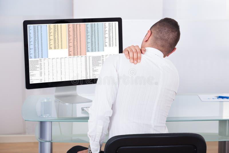 Бизнесмен с болью плеча используя компьютер стоковое фото