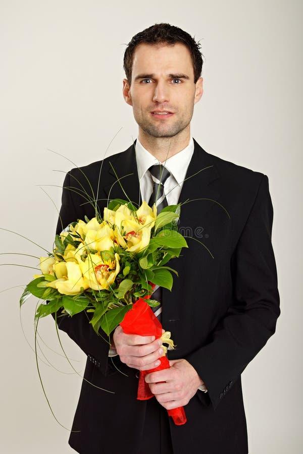Бизнесмен с букетом орхидеи стоковые фотографии rf