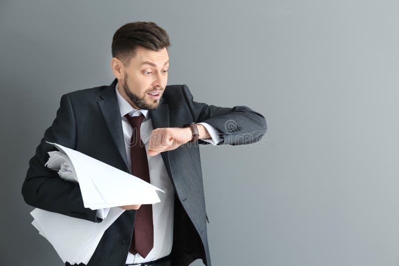 Бизнесмен с бумагами смотря его наручные часы на серой предпосылке Концепция контроля времени стоковое фото