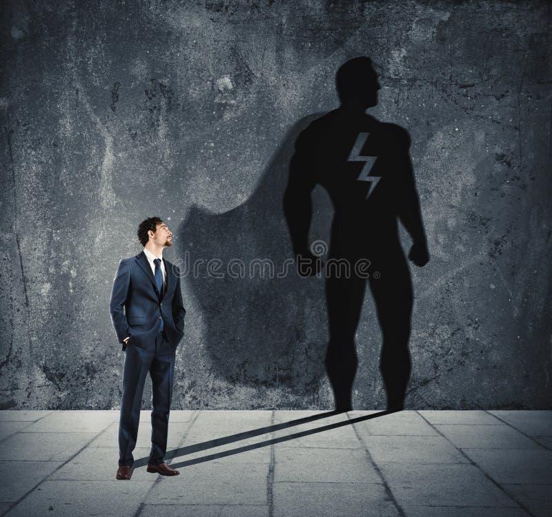Бизнесмен с его тенью супергероя на стене Концепция мощного человека стоковые фотографии rf