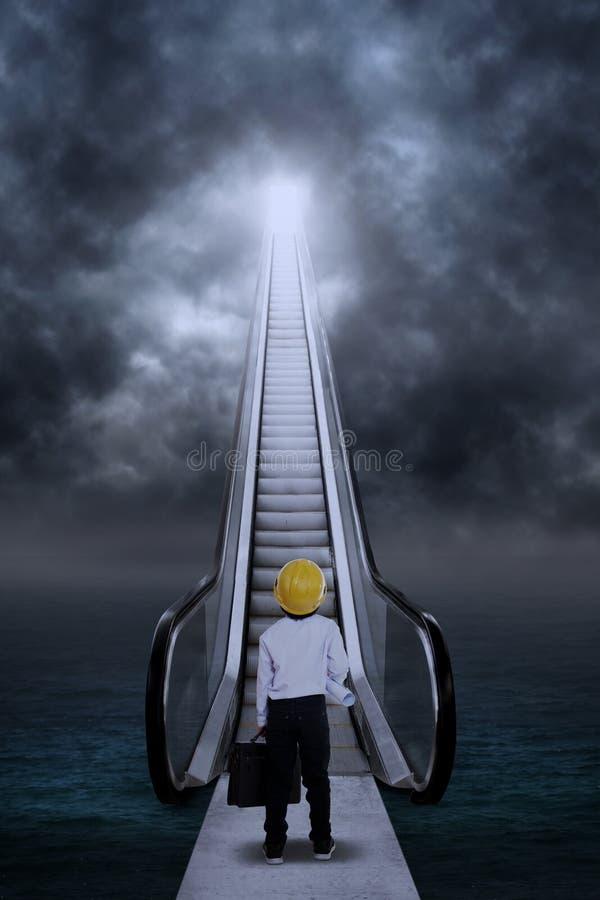 Бизнесмен с золотой головой яичка на эскалаторе стоковые изображения rf