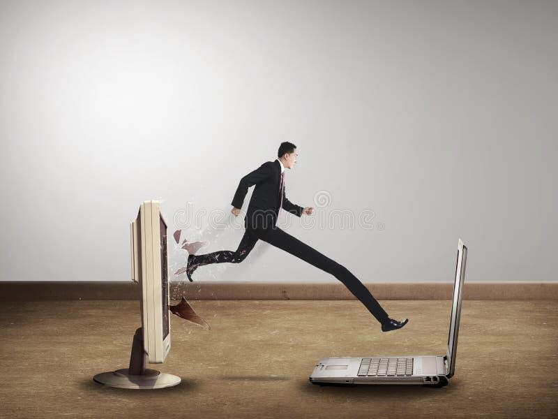Бизнесмен с длинной ногой вне от настольного компьютера компьютера к компьтер-книжке стоковое фото rf