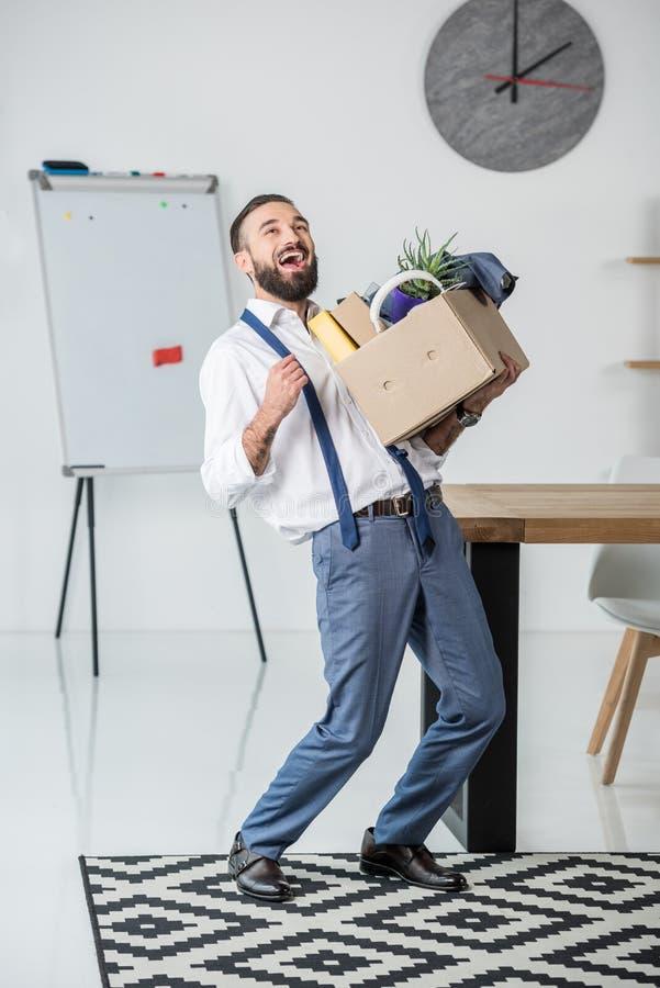 Бизнесмен с картонной коробкой в руках прекращая работу стоковое изображение rf
