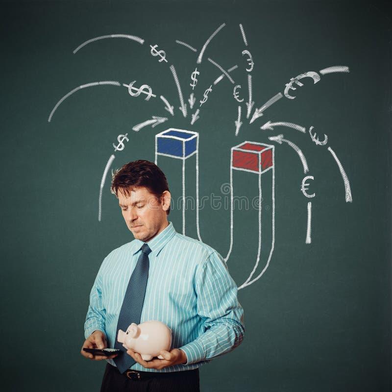 Бизнесмен с калькулятора, копилки и денег магнита задней частью дальше стоковая фотография rf