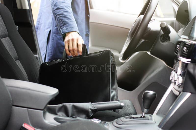 Бизнесмен с кожаным портфелем сидит на сидении водителя в автомобиле  стоковые изображения