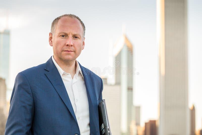 Бизнесмен с компьтер-книжкой перед офисными зданиями стоковое фото rf