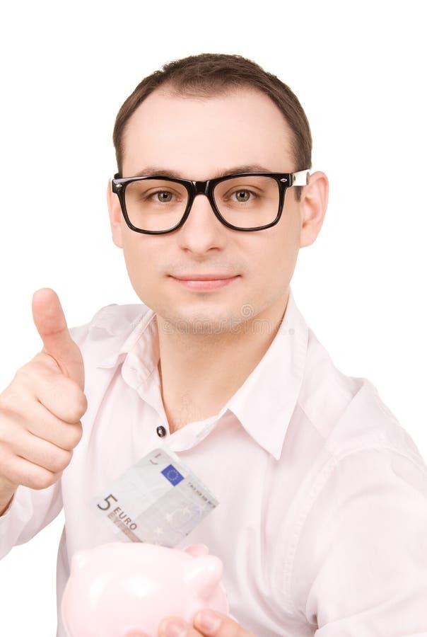 Бизнесмен с копилкой и деньгами стоковое фото