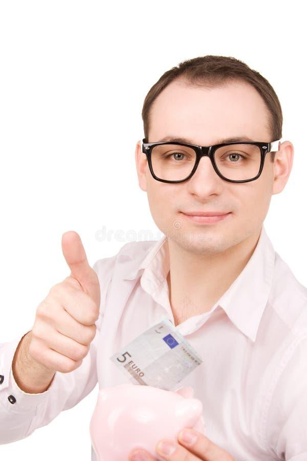 Бизнесмен с копилкой и деньгами стоковые изображения