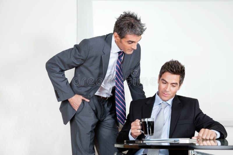 Бизнесмен с кофейной чашкой в встрече с стоковое изображение