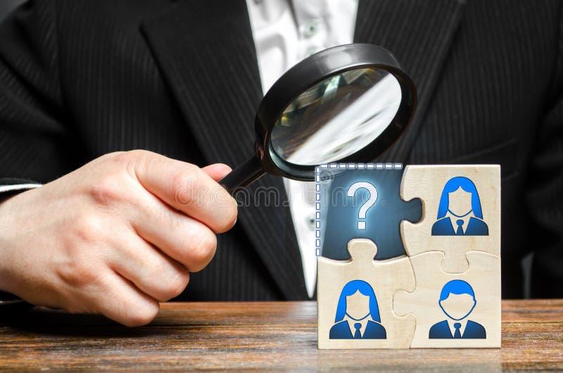Бизнесмен с лупой рассматривает отсутствующую часть команды головоломки Поиск, штат рекрутства, нанимая руководитель стоковая фотография