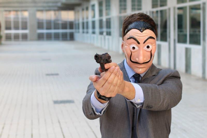 Бизнесмен с маской держа оружие стоковые изображения rf