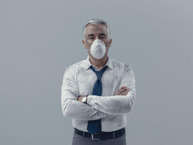 Бизнесмен с маской загрязнения стоковые изображения