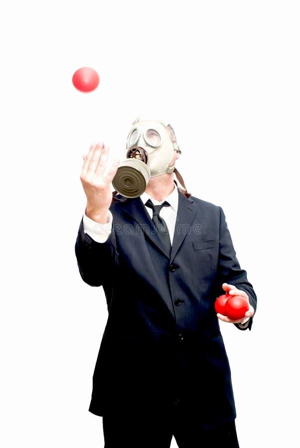 Бизнесмен с маской противогаза которая жонглирует с красными шариками стоковые фото