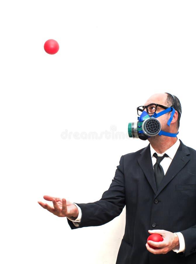 Бизнесмен с маской противогаза которая жонглирует с красными шариками стоковое фото