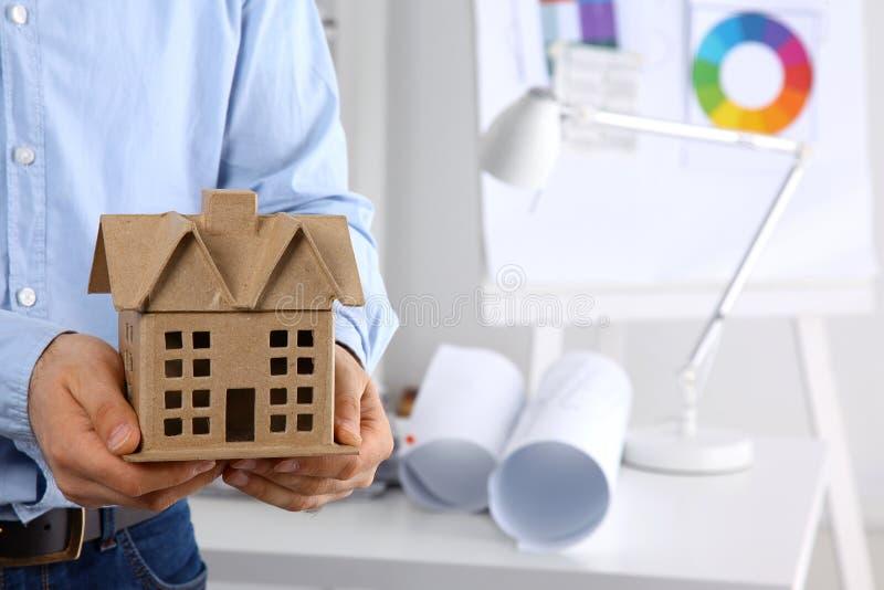 Бизнесмен с миниатюрой дома в руке стоя в офисе стоковые изображения