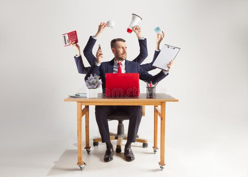 Бизнесмен с много рук в элегантном костюме работая с бумагой, документом, контрактом, папкой, бизнес-планом стоковые изображения