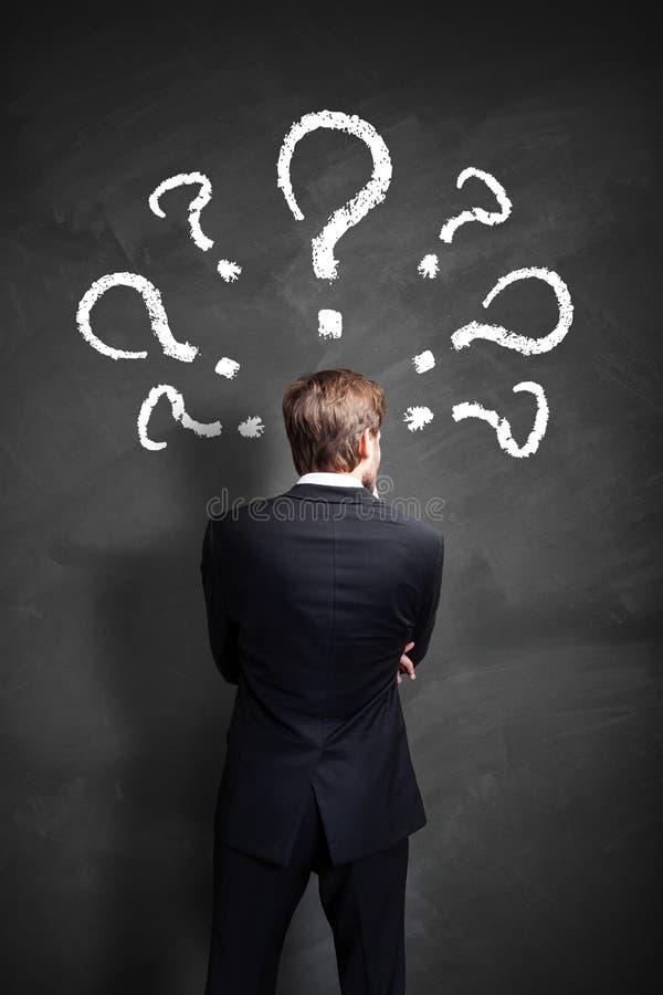 Бизнесмен с много questionmarks над его головой стоковые изображения rf