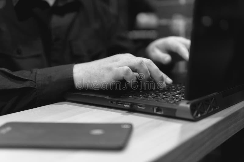 Бизнесмен с ноутбуком использует мобильную телефонную связь в кафе Взгляд nighttime с улицы Темная тема, в черном стиле Гай стоковые фото