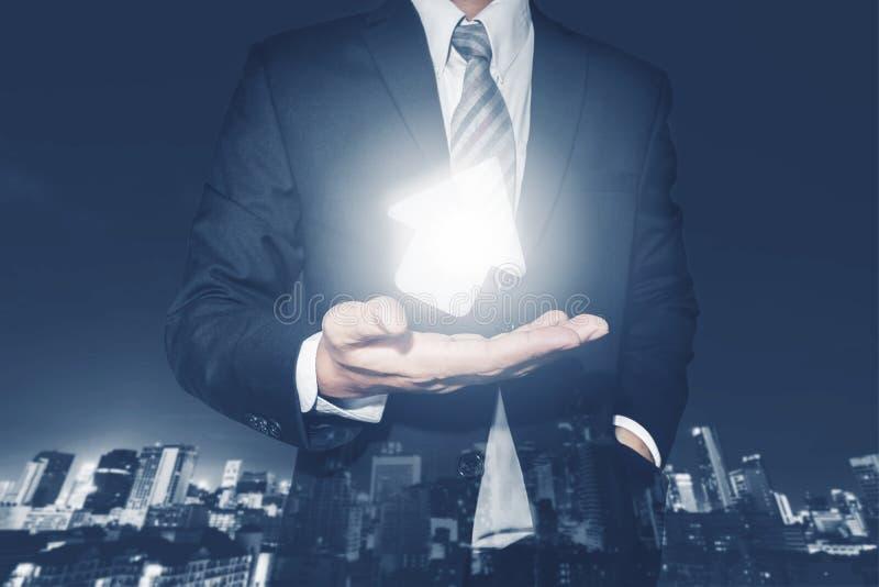 Бизнесмен с поворотом вверх по яркой стрелке в наличии, с предпосылкой города ночи defocus стоковые изображения
