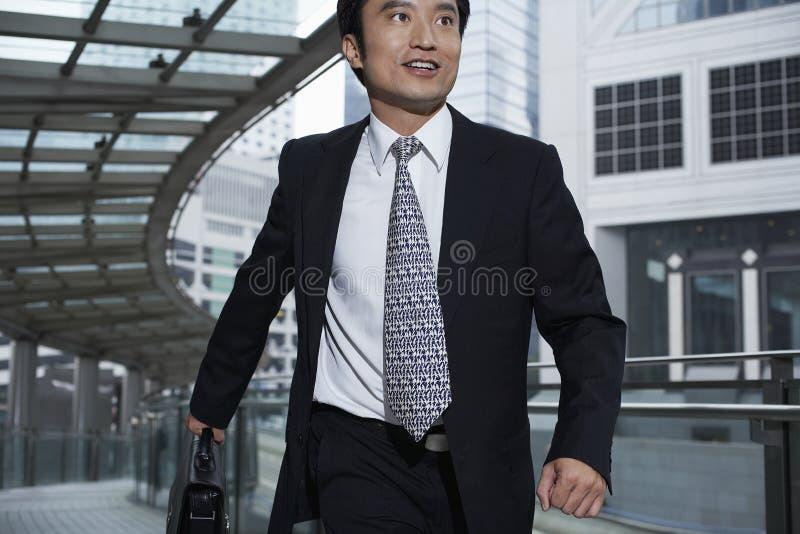 Бизнесмен с портфелем идя на Footbridge стоковые фото