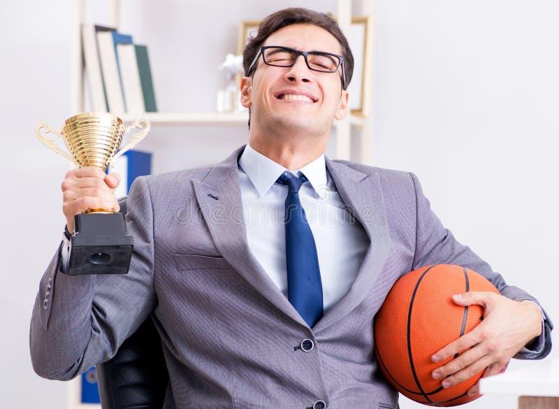 Бизнесмен с призовой чашкой для достижений в офисе стоковая фотография