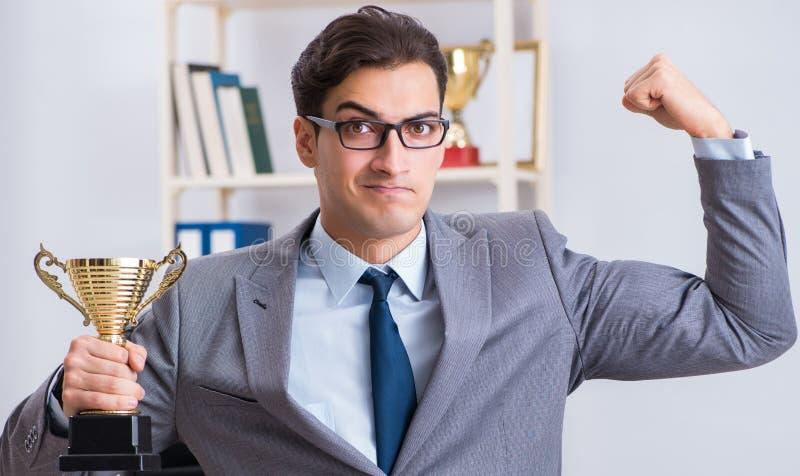 Бизнесмен с призовой чашкой для достижений в офисе стоковое фото rf