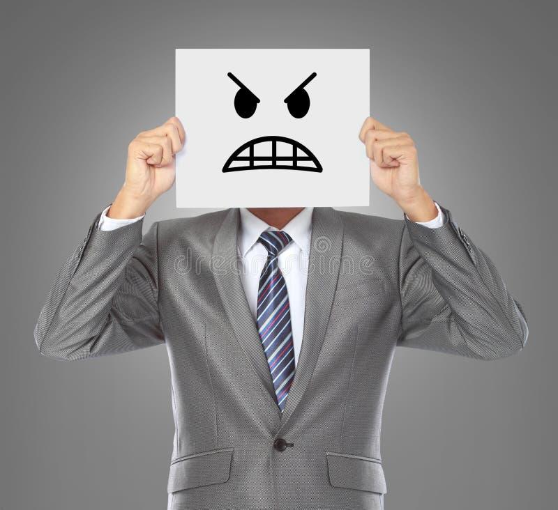 Бизнесмен с сердитой маской стоковое фото