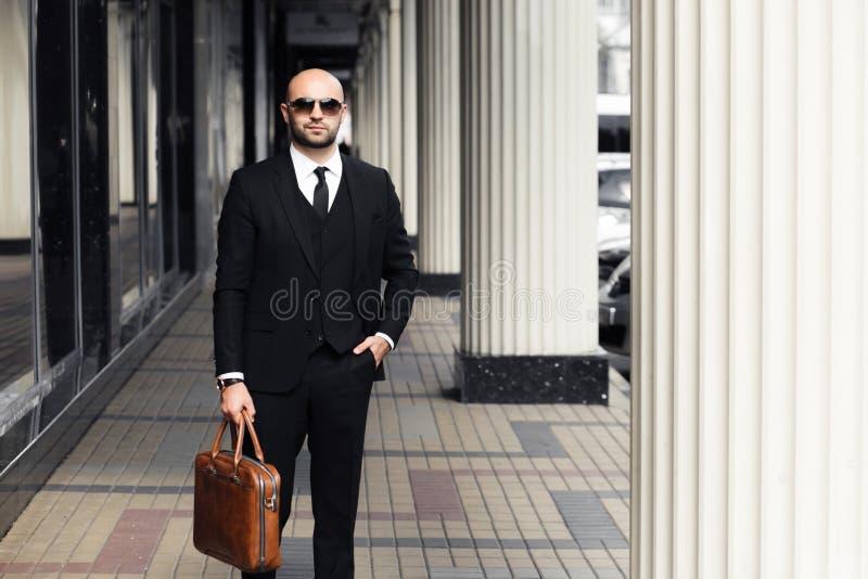 Бизнесмен с сумкой около офиса стоковое изображение