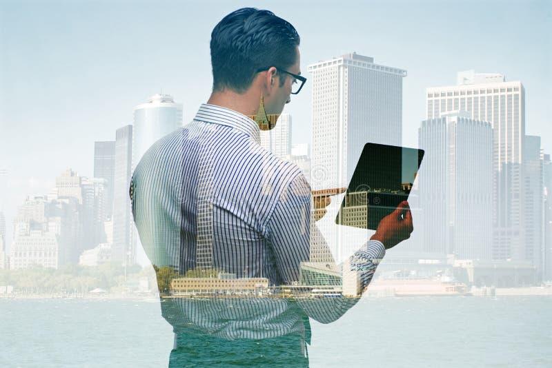 Бизнесмен с таблеткой против зданий стоковое изображение
