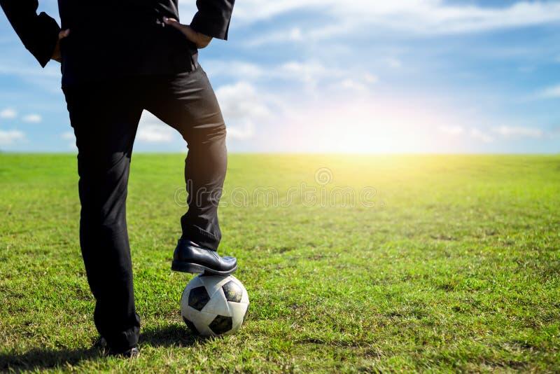 Бизнесмен с футбольным мячом на тангаже стоковое изображение